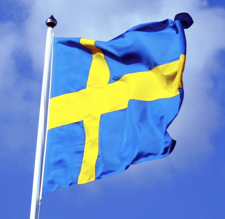 Swedish flag with blue sky behind commons.wikimedia